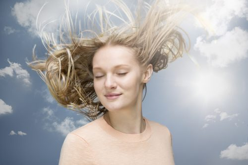 Young woman shaking her hair in wind